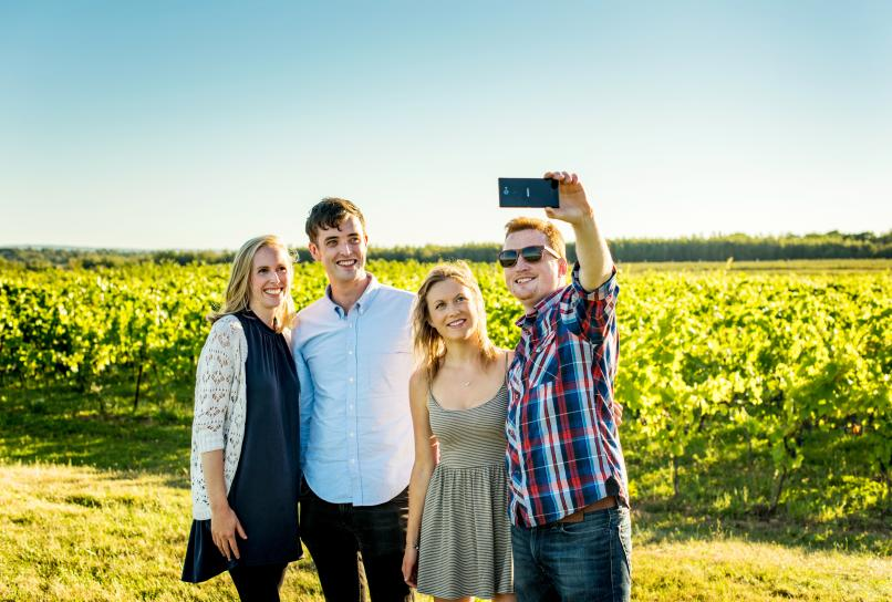 Visitors taking a selfie photo in a Nova Scotia vineyard.