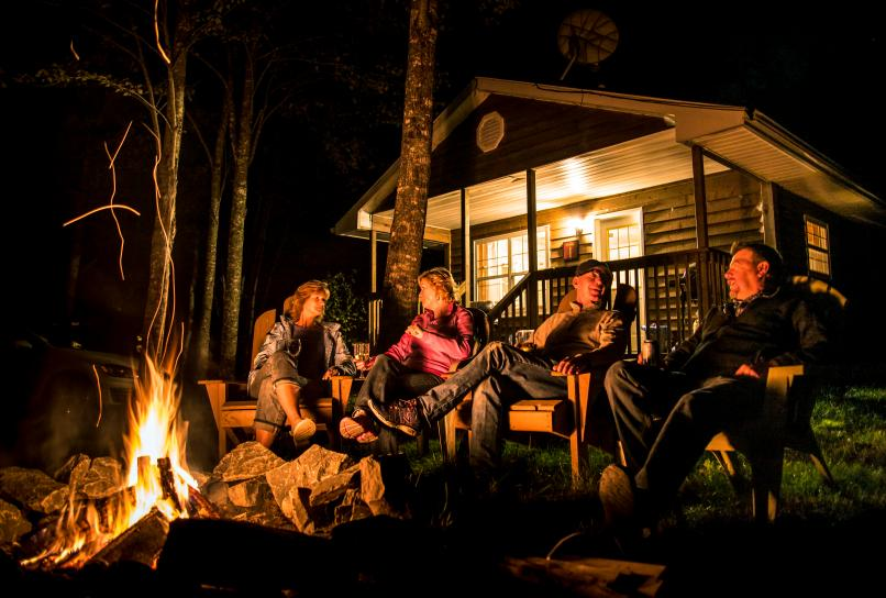 Visitors by the campfire at their cottage accommodation.
