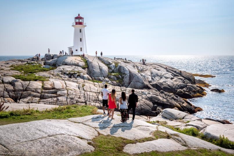 Group standing on the rocks at Peggys Cove looking out at the lighthouse.